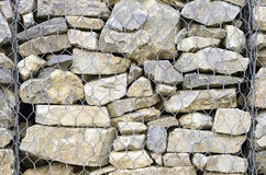 Particular of the retaining wall gabion. Retaining drywall, built of stone filling a container made from a wire mesh hexagonal mesh, said gabion Stock Image