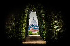 A particular view of the dome of St. Peter Vatican City - Rome. Continuing after the Giardino degli Aranci, at Piazza Cavalieri di Malta there is the Villa del Royalty Free Stock Image