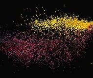 Particules minuscules colorées au-dessus d'un fond foncé photographie stock