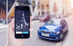 Partida da aplicação de Uber na exposição do iPhone de Apple na mão fêmea Imagens de Stock Royalty Free
