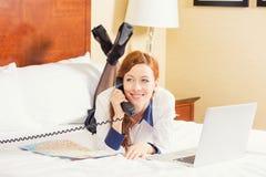 Partida del día de fiesta de la reservación de la mujer que pone en cama con el ordenador portátil del mapa que habla en el teléf foto de archivo libre de regalías