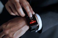 Partida do botão da imprensa do homem de negócios no relógio esperto fotos de stock royalty free