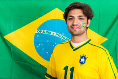 Partidario brasileño confiado que se coloca delante del brasilen@o Fla Foto de archivo