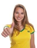 Partidario brasileño sonriente del fútbol que muestra golpe para arriba Imágenes de archivo libres de regalías