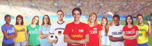 Partidario del fútbol de España con las fans otros países en el estadio imagenes de archivo
