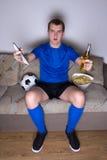 Partidario emocional del fútbol que ve la TV con la cerveza y los microprocesadores Imágenes de archivo libres de regalías