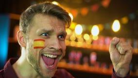 Partidario español feliz del fútbol con la bandera en la mejilla que grita, meta que anota del equipo almacen de metraje de vídeo