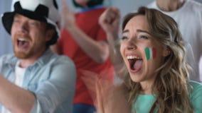 Partidarios italianos que miran el juego en el equipo nacional de la TV, del grito y del apoyo metrajes