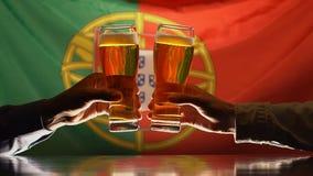 Partidarios masculinos del deporte que tintinean los vidrios de cerveza, bandera portuguesa en fondo metrajes