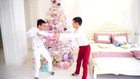 Partidas criançolas de dois irmãos dos gêmeos e da luta inocente para o presente de Natal no quarto com árvore de Natal filme