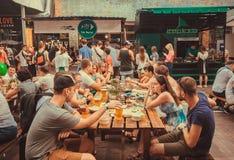 Partido amigável com a multidão de comer povos na tabela durante o festival exterior do alimento da rua Fotografia de Stock Royalty Free