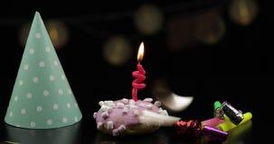 Partido Bu?uelo rosado y una vela festiva roja en ella Ca?da de oro del confeti metrajes