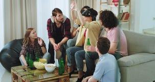 Partido casero en los amigos étnicos multi de la sala de estar que beben la cerveza y que usan un VR a explorar un mundo virtual, metrajes