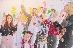 Partido colorido de la Feliz Año Nuevo en hombres de negocios de la oficina fotos de archivo