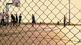 Partido de baloncesto durante puesta del sol almacen de video