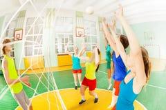 Partido de balonvolea con el grupo de adolescencias en pasillo de deportes Fotos de archivo