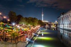Partido de Berlin Strandbar en el r?o de la diversi?n con la torre en la noche, Alemania de la TV foto de archivo