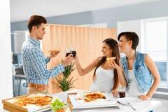 Partido de cena Amigos felices que comen la pizza, divirtiéndose Amistad Fotos de archivo