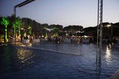 Partido de cena por la piscina en la puesta del sol Imagen de archivo