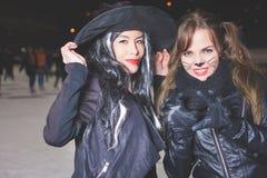 Partido de Dia das Bruxas! As jovens mulheres gostam do papel da bruxa e do gato Imagens de Stock Royalty Free