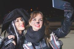 Partido de Dia das Bruxas! As jovens mulheres gostam do papel da bruxa e do gato Imagem de Stock Royalty Free