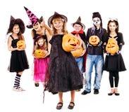 Partido de Dia das Bruxas com a criança do grupo que guarda a cinzeladura da abóbora. Imagens de Stock Royalty Free
