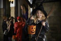 Partido de Dia das Bruxas com truque ou tratamento das crianças no traje Foto de Stock