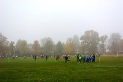 Partido de fútbol del fútbol para los niños en niebla foto de archivo