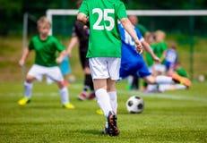 Partido de fútbol del fútbol de la juventud Muchachos que golpean el balón de fútbol con el pie Fotos de archivo