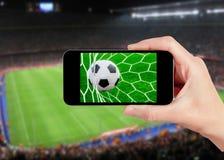 Partido de fútbol en el teléfono móvil Imágenes de archivo libres de regalías