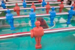 Partido de fútbol de la tabla con los jugadores rojos y azules foto de archivo