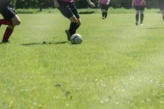 Partido de fútbol de los equipos de deportes del ` s de las mujeres en un campo de fútbol verde Foto de archivo libre de regalías