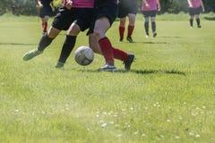 Partido de fútbol de los equipos de deportes del ` s de las mujeres en un campo de fútbol verde Fotografía de archivo