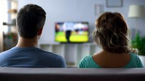 Partido de fútbol de observación agujereado de los pares en la TV, conflicto, pasatiempo pasivo junto imagenes de archivo