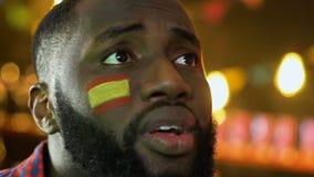 Partido de fútbol de observación decepcionado del hombre negro, bandera española en la mejilla, pérdida almacen de video