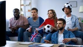 Partido de fútbol de observación de los amigos británicos multiétnicos en casa, apoyando al equipo fotografía de archivo