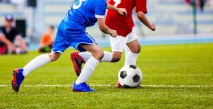 Partido de fútbol para los niños Niños que juegan al juego de torneo del fútbol Imagen de archivo libre de regalías