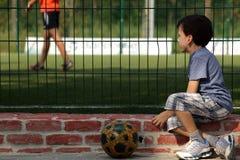 Partido de fútbol de observación del niño joven del muchacho para la rejilla Imágenes de archivo libres de regalías