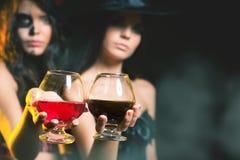 ¡Partido 2016 de Halloween! Las mujeres de la moda les gusta la bruja que sostiene el cóctel Imagen de archivo