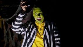 Partido de Halloween, noche, crepúsculo, en los rayos de la luz, un hombre con un maquillaje terrible, con liftinges faciales ver metrajes