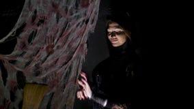 Partido de Halloween, noche, retrato espantoso de una muchacha en un traje del gato, en el crepúsculo, en los rayos de la luz ell almacen de metraje de vídeo