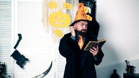 Partido de Halloween y concepto de la celebración Un hombre barbudo en un sombrero y en un impermeable negro lee el libro viejo y almacen de metraje de vídeo