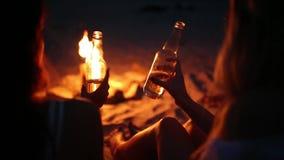Partido de la playa en la puesta del sol con la hoguera Amigos que se sientan alrededor de la hoguera, cerveza de consumición y c almacen de video