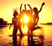 partido de la playa Muchachas felices en agua sobre puesta del sol imagen de archivo