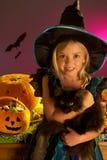Partido de Víspera de Todos los Santos con un niño que sostiene el gato negro Fotos de archivo libres de regalías