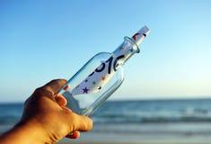 Partido del Año Nuevo, botella con el mensaje en la playa, 2016 Foto de archivo libre de regalías