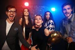 Partido del Año Nuevo, días de fiesta, celebración, vida nocturna y concepto de la gente - gente joven que tiene baile de la dive Foto de archivo libre de regalías