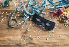 Partido del carnaval Máscara, confeti y serpentinas en el fondo de madera, niew superior Imagen de archivo