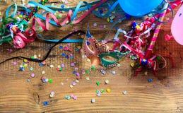 Partido del carnaval Máscara, confeti y serpentinas en el fondo de madera, niew superior Fotos de archivo libres de regalías