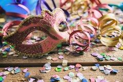 Partido del carnaval Máscara, confeti y serpentinas en fondo de madera Fotos de archivo libres de regalías